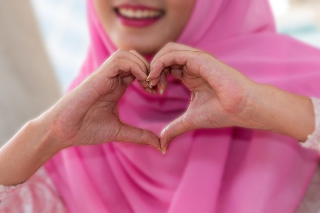 Portrait of beautiful happy arab muslim woman holding heart shaped hands in pink hijab clothing traditional .Showing love sign with valentine day concept; Shutterstock ID 1005743062