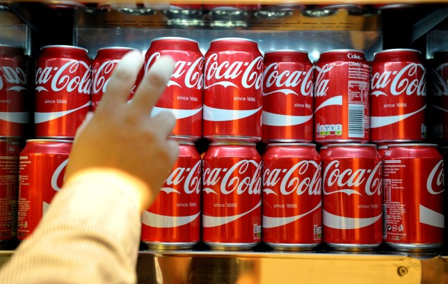Cans of Coca-Cola which would currently fall within the higher rate of the sugar tax, following the announcement of a tax on sugary drinks, unveiled by George Osborne as part of the Budget.