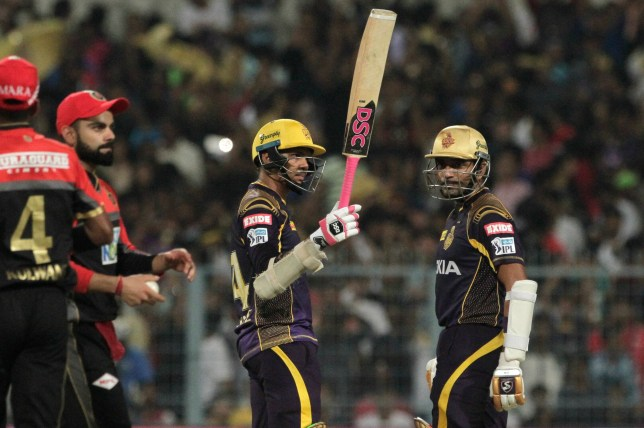 Kolkata Knight Riders' Sunil Narine, center acknowledges the crowd after scoring fifty runs during VIVO IPL cricket T20 match against Royal Challengers Bangalore in Kolkata, India, Sunday, April 8, 2018. (AP Photo/Bikas Das)