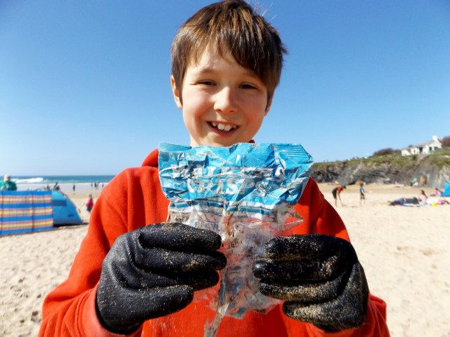Laurence Miller (10) with the packet of crisps. Beach-cleaning volunteers were left shocked when they discovered a Walkers crisp packet from the 1980s washed up on the shore. See NTI story NTICRISPS. The largely intact bag of cheese and onion flavoured crisps was found as part of an initiative to clear the coastline of rubbish. Despite not having a printed date still visible on the packet, research by the Beach Guardian project, who cleaned around 20kg from the beach, estimates it as being produced in the late 1980s. Laurence Miller, aged ten, found the packet - which is around three times older than him - on Treyarnon Bay, in Padstow, Cornwall on Sunday (8/4).