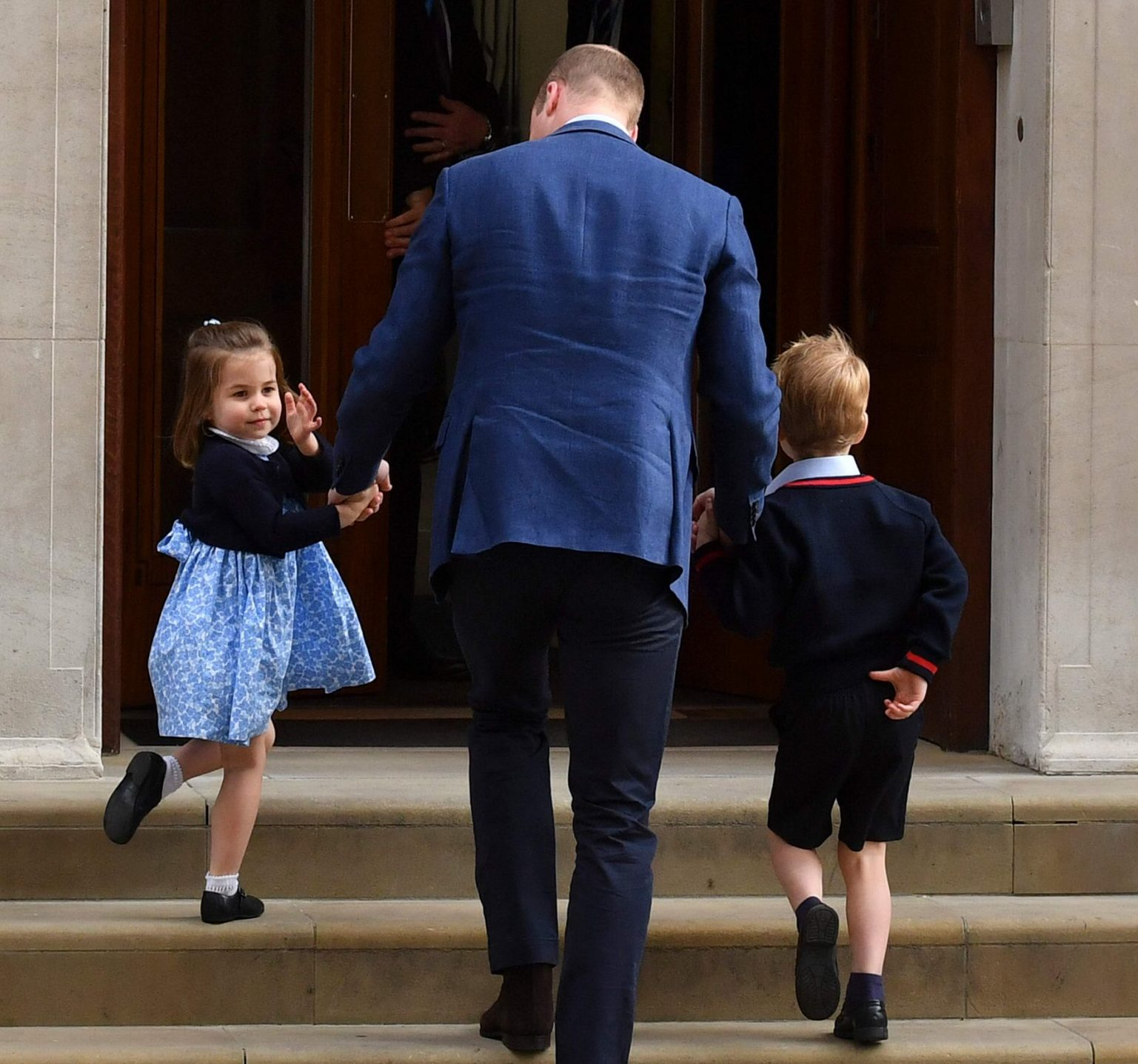 """Princess Charlotte of Cambridge (L) turns to wave at the media as she is lead in with her brother Prince George of Cambridge (R) by their father Britain's Prince William, Duke of Cambridge, (C) at the Lindo Wing of St Mary's Hospital in central London, on April 23, 2018, to visit Catherine, Duchess of Cambridge, and their new-born son. Kate, the wife of Britain's Prince William, has given birth to a baby son, Kensington Palace announced Monday. """"Her Royal Highness The Duchess of Cambridge was safely delivered of a son at 11:01 (1001 GMT),"""" the palace said in a statement. The baby boy weighs eight pounds and seven ounces (3.8 kilogrammes). / AFP PHOTO / Ben STANSALLBEN STANSALL/AFP/Getty Images"""