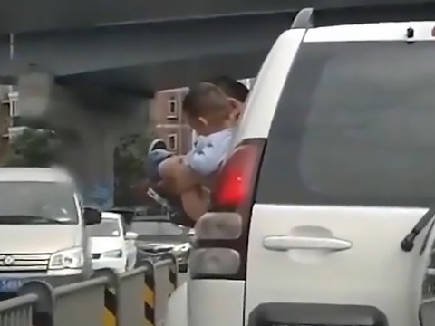 Father holds son from car window so he can have a wee at traffic lights