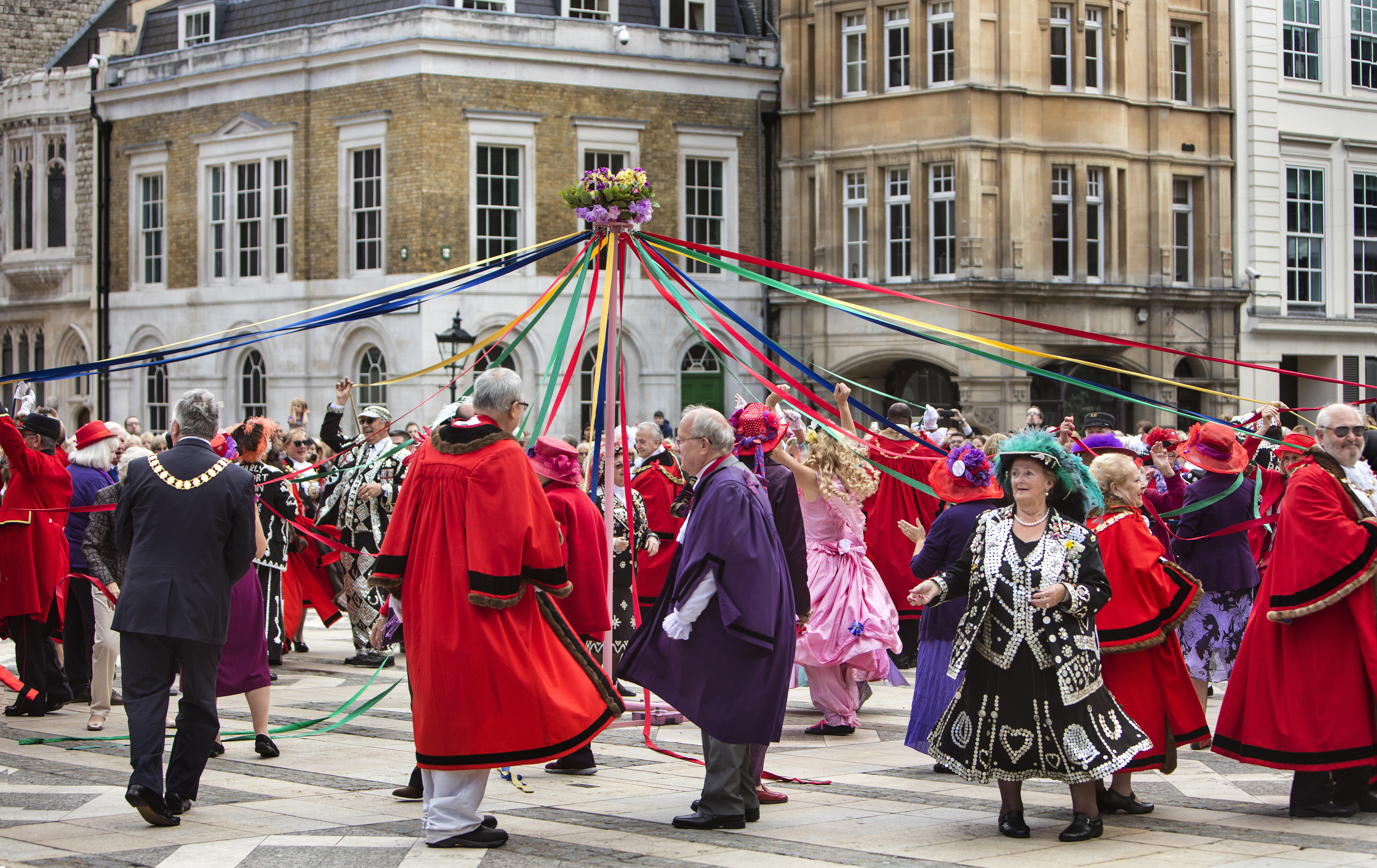 People celebrating May Day dance round a maypole