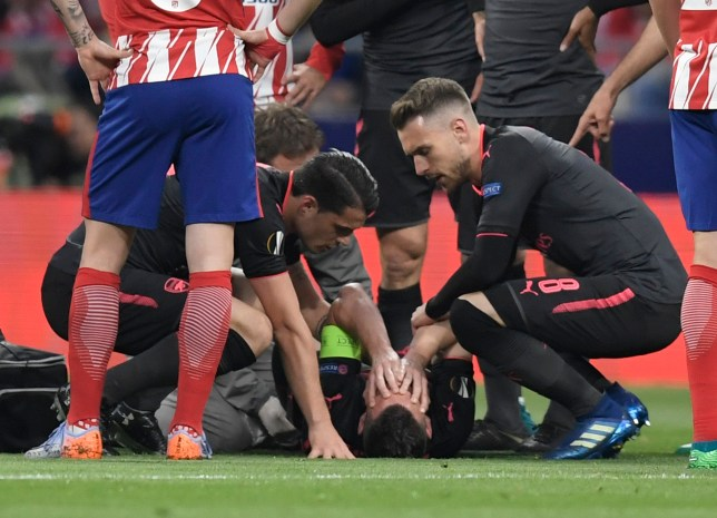 Arsenal's French defender Laurent Koscielny (bottom) lies on the field during the UEFA Europa League semi-final second leg football match between Club Atletico de Madrid and Arsenal FC. / AFP PHOTO / GABRIEL BOUYSGABRIEL BOUYS/AFP/Getty Images
