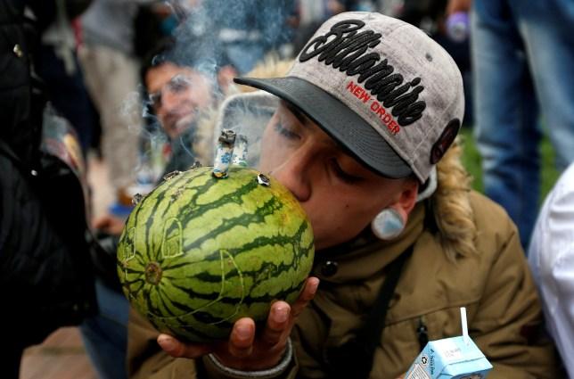 A man smoking marijuana through a watermelon during a Global March for marijuana in Bogota, Colombia, May 5, 2018. REUTERS/Jaime Saldarriaga