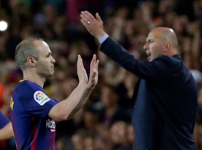 Barcelona's Andres Iniesta greets his substitute as Real Madrid's head coach Zinedine Zidane, right gives directions to his team during a Spanish La Liga soccer match between Barcelona and Real Madrid, dubbed 'El Clasico', at the Camp Nou stadium in Barcelona, Spain, Sunday, May 6, 2018. (AP Photo/Emilio Morenatti)