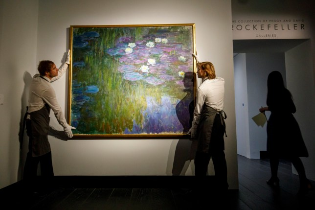 epa06719523 (FILE) - Gallery assistants pose with the painting 'Nympheas en fleur' by French artist Claude Monet during a photocall at Christie's auction house in London, Britain, 20 February 2018. The artwork is part of the Collection of Peggy and David Rockefeller: 19th and 20th Century Art Evening Sale in New York that takes place from 08 to 10 May 2018. EPA/TOLGA AKMEN *** Local Caption *** 54138970