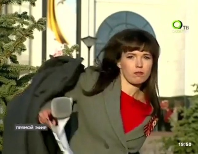 """Pic shows: Maria Ryabova, the journalist throws away her coat. This is the moment a TV journalist suddenly found herself unexpectedly on camera and promptly threw her coat into a bush. Maria Ryabova had the coat wrapped loosely around her to keep warm as she waited to give a story to camera in the city of Yuzhno-Sakhalinsk in far eastern Russia's Sakhalin Oblast region. Suddenly she found herself on live television and being shouted at by her producer who told her: """"Take off your coat! Throw it on the ground!"""" Ms Ryabova jumped with a start, whipped off the coat, turned around and threw it under the bush she was standing in front of. She then did her best to resume her professionalism, by putting on her best smile and continuing with her story about celebrations to mark Victory Day in Russia. Ms Ryabova was covering tributes to the war dead in Yuzhno-Sakhalinsk for the local Russian TV Channel, OTV Sakhalin. Victory Day is a major public holiday which marks the anniversary of the end of the Great Patriotic War, as World War II is known in Russia. It marks the surrender of Nazi Germany in 1945 which happened late in the evening of 8th May but is marked in Russia on 9th May as it was after midnight in Moscow. (ends)????????????????????"""