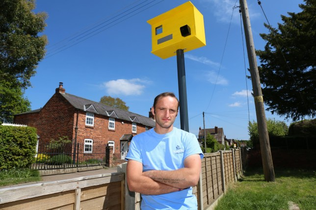 PIC BY James Ward/Caters_News - (PICTURED: James Dyke and his Fake Speed Camera he created to deter speeding traffic. Clows Top, Worcestershire) - desperate home owner has created his own speed camera for 25 to trick fast drivers into slowing down. Creative Jim Dyke, 32, was so fed up of drivers speeding up to 60mph past his home in, Clows Top, Kidderminster, that he decided to take matters into his own hands.After visiting his local DIY store, Jim purchased one drain pipe, screws, a gutter fitting, ply wood, yellow paint and a mirrored beer mat - totaling just 25.). SEE CATERS COPY