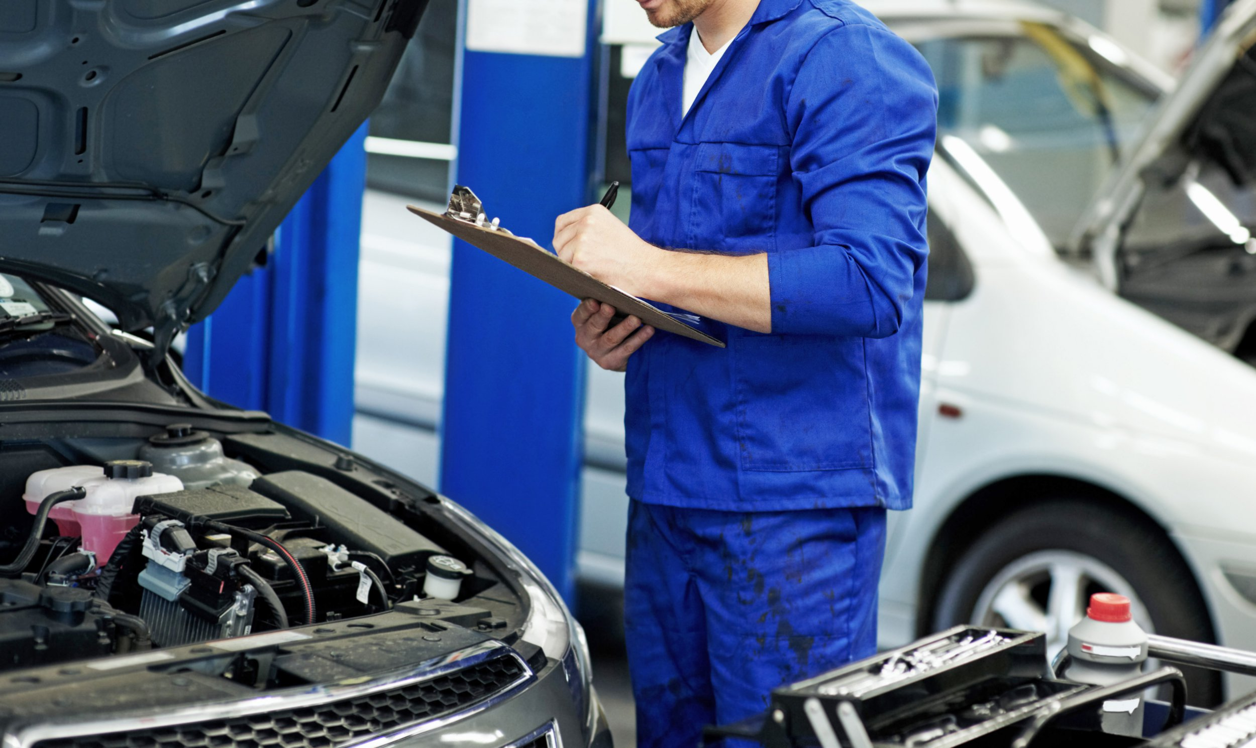 Mechanic making notes on a clipboard during a car service at his workshop