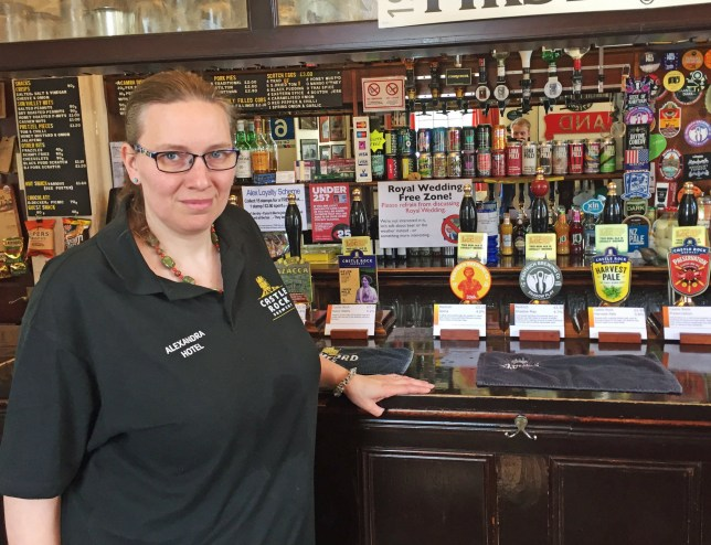 "Landlady Anna Dyson-Edge at The Alexandra Hotel in Derby, which has banned any mention of the royal wedding on Saturday, with a ""swear"" box installed for anyone who talks about the ceremony. PRESS ASSOCIATION Photo. Picture date: Thursday May 17, 2018. The landlady said regulars were ""sick of hearing"" about Prince Harry and Meghan Markle's wedding so she decided to put posters up around the pub of the couple with a red cross through it. See PA story ROYAL Wedding Ban. Photo credit should read: Josh Payne/PA Wire"
