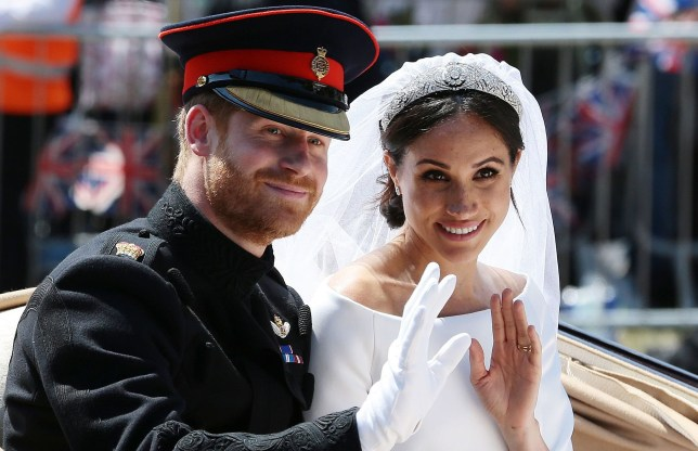 TOPSHOT - Britain's Prince Harry, Duke of Sussex and his wife Meghan, Duchess of Sussex wave from the Ascot Landau Carriage during their carriage procession on the Long Walk as they head back towards Windsor Castle in Windsor, on May 19, 2018 after their wedding ceremony. / AFP PHOTO / POOL / Aaron ChownAARON CHOWN/AFP/Getty Images
