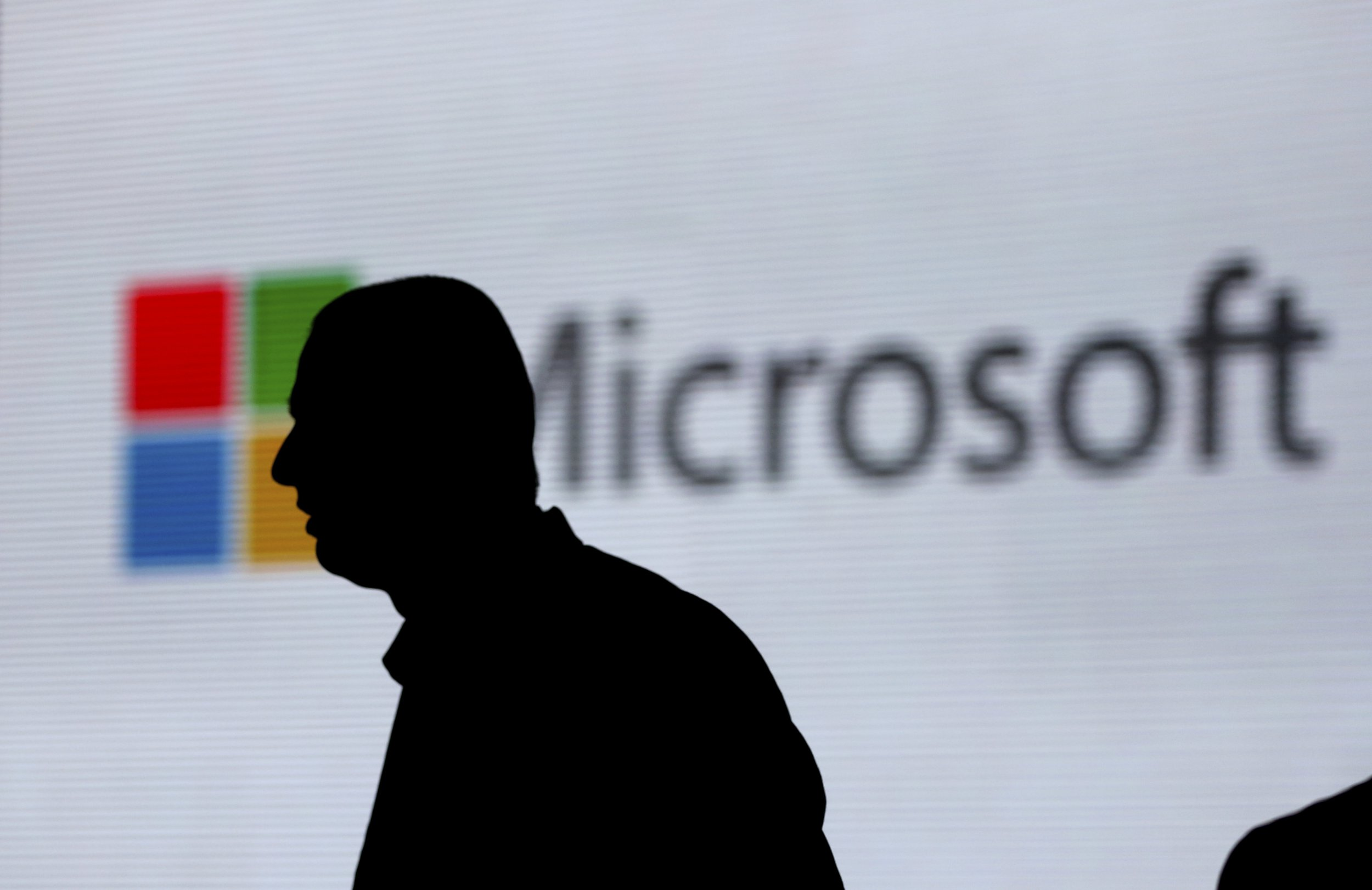 FILE - In this Nov. 7, 2017, file photo, an unidentified man is silhouetted as he walks in front of Microsoft logo at an event in New Delhi, India. Microsoft says it's committing to giving users worldwide the same data and privacy rights being offered to Europeans under new regulations there. That means no matter where you live, you'll be able to see what Microsoft collects about you and correct or delete that information if necessary. (AP Photo/Altaf Qadri, File)