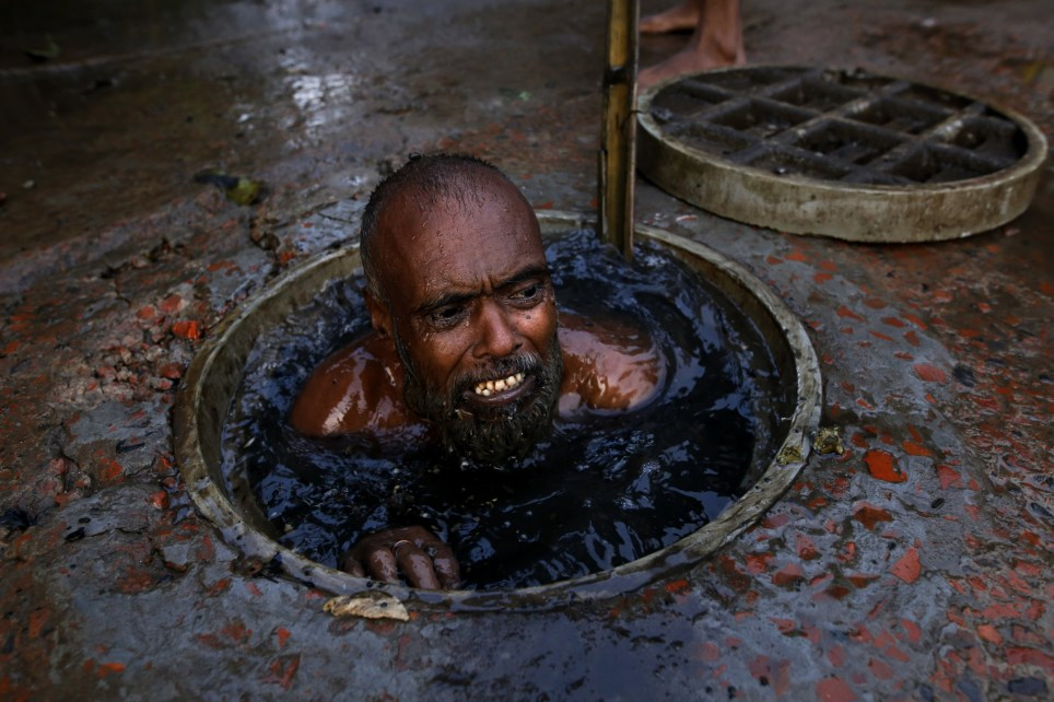 Dhaka, Bangladesh. A sewer cleaner is cleaning sewer without any safety stuff in Dhaka, Bangladesh on May 23, 2018. Sewer cleaners earn 6 to 10 US dollar a day as they doing risky, worst job in Dhaka. Every year many of sewers cleaner have died as they doing job. In the rainy season in the capital city, sewerage lines packed by rubbish as residents have been suffering from it and water-logged in the city. Meanwhile sewer cleaning is the worst job in the world. PHOTOGRAPH By Rehman Asad/Barcroft ImagesPHOTOGRAPH BY Rehman Asad / Barcroft Images