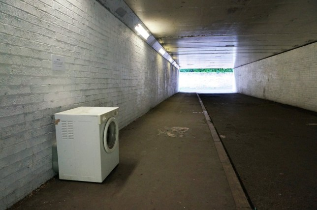 """The art installation in Oxford by @Athirty4. See SWNS story SWWASHER; A street artist who left a washing machine in an underpass will see it removed - after the council branded it FLYTIPPING. The washer was abandoned by local artist Athirty4 next to a clothes hook on which passersby are asked to """"hang their sorrows"""". The washing machine, removed by council workers yesterday (Thurs), sat next to a sign referencing """"preconceptions"""" about modern art in Littlemore, Oxford. Tom Hayes, the city council's greener environment boss, said: ?The washing machine is blocking the public highway."""