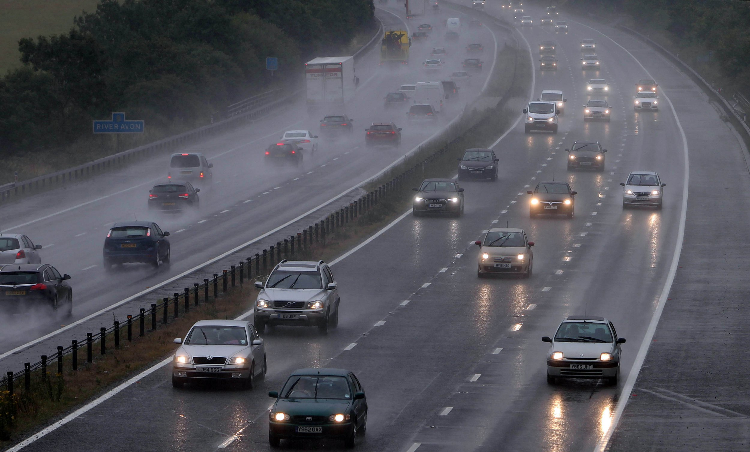 """Cars drive along the M4 Motorway in the rain near Chippenham, Wiltshire, as parts of Britain are battered by very heavy rain and winds of up to 50mph in an """"intense"""" day of unseasonably bad weather."""