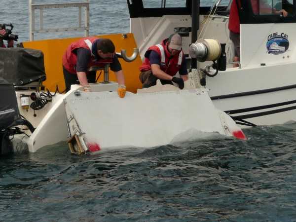 FILE PHOTO: A Boeing 777 flaperon cut down to match the one from flight MH370 found on Reunion island off the coast of Africa in 2015, is lowered into water to discover its drift characteristics by Commonwealth Scientific and Industrial Research Organisation researchers in Tasmania, Australia, in this handout image taken March 23, 2017. CSIRO/Handout/File Photo via REUTERS ATTENTION EDITORS - THIS IMAGE HAS BEEN SUPPLIED BY A THIRD PARTY.