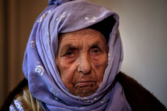 Laila Saleh, a 110 years old Syrian refugee from Kobane, poses for photographes, in Athens on December 15, 2017. Laila Saleh, who was born in Kobane on 1907, also made the dangerous crossing of the Aegean sea with an inflatable boat. She hopes to see again her granddaughter Nasrin, a refugee who found shelter in Germany. Laila Saleh arrived on the Greek island of Lesbos in early November with her grandson Halil, her youngest son Ahmad, Halil's father, her daughter-in-law, and Halil's wife and their two children. / AFP PHOTO / ARIS MESSINIS (Photo credit should read ARIS MESSINIS/AFP/Getty Images)