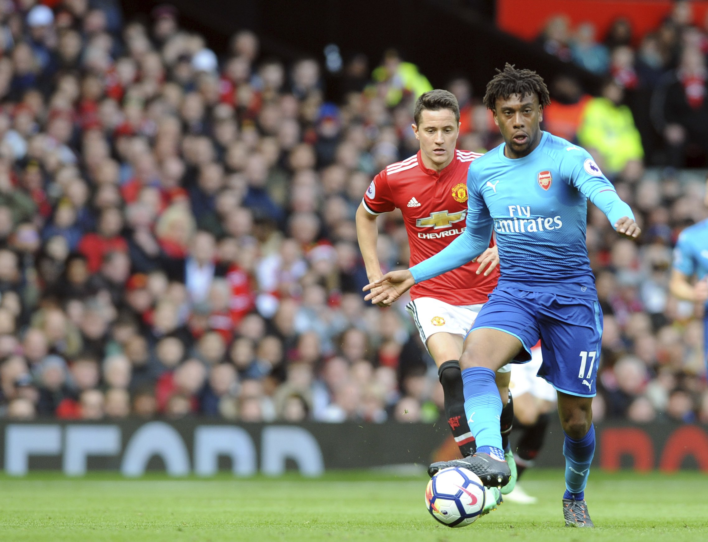 Arsenal's Alex Iwobi, right, and Manchester United's Ander Herrera run for the ball during the English Premier League soccer match between Manchester United and Arsenal at the Old Trafford stadium in Manchester, England, Sunday, April 29, 2018. (AP Photo/Rui Vieira)