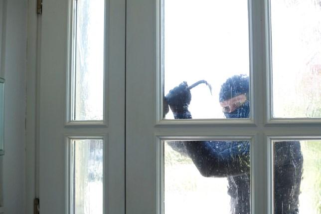 Burglar with crowbar breaking front door