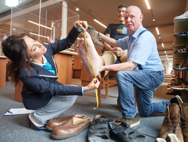 """04 June 2018, Vreden, Germany: The right foot of Jeison Rodriguez, the man with the world's biggest feet, is being measured by Lucia Sinigagliesi, Judge of the Guniess World Records and Georg Wessels of the Oversized shoe making workshop """"Wessels"""". The 22 year- old from Venezuela wears a size 68 and has had his shoes specially made for him by a Shoemaker from Vreden (near the Borders of Netherlands) for the past 5 years. Guiness World Records has confirmed on June 4, 2018 that his massive feet with 40.55 cm left and 40.57 cm right are still the world's biggest feet. Photo: Bernd Thissen/"""