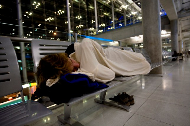 A male traveler sleeps on a bench in the Bangkok International Airport in Bangkok, Thailand on March 12, 2007.