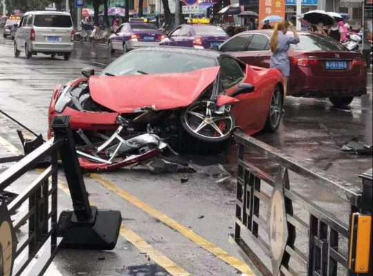 """Pic shows: The woman driver stands behind her wrecked Ferrari rental This is the moment a bungling woman driver destroys a Ferrari 458 after losing control of the sports car worth nearly half a million GBP and slamming into a BMW. Incredible footage circulating on social media has also allegedly captured the woman bragging about behind the wheel of the pricey supercar, which she rented from a dealership in Wenling city in China???s eastern Zhejiang province. In the short clip believed to have been filmed by the woman while she was waiting at the lights, she points the camera at the Ferrari???s dashboard and says: """"First time driving a Ferrari. This truly is the most amazing feeling."""" But traffic cameras on the busy city-centre road shows the woman suddenly swerving out of control and slamming head-on into a metal traffic barrier and a BMW X3, which also collides with the unsuspecting driver of a black Nissan saloon car. In spite of what appeared to be a low-speed crash, footage taken by witnesses in the aftermath of the accident showed the front end of the Ferrari 458 completely destroyed and its airbags deployed. She and her female passengers were not seriously injured. The vehicle is reported to have been purchased by the rental dealership for the astronomical import price of more than 4 million RMB (463,000 GBP), while the cost to mend the damaged Italian sports car has been estimated at half that amount. It is unclear if the woman was insured and whether it would cover the damage. Social media users have suggested the woman may have turned off the car???s traction control before the crash, which would explain how the vehicle suddenly spun out of control. Netizen ???Lutaichang 921??? wrote: """"See, Ferraris have terrible build quality - that???s why I haven???t bought one"""" followed by an emoji of a winking face."""
