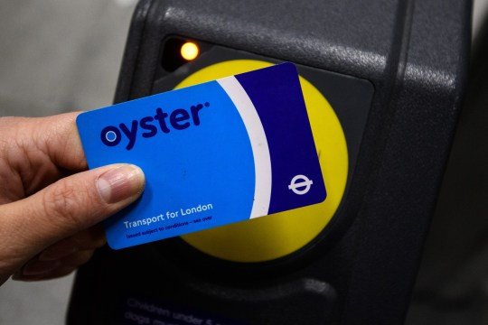 LONDON, ENGLAND - NOVEMBER 18: A woman poses for a photgraph with an Oyster card at a ticket barrier at Tottenham Court Road underground station on November 18, 2016 in London, England. London mayor Sadiq Khan has frozen pay-as-you-go fares until the end of 2020 and has urged the government to do the same for rail fares on services in and out of the capital. (Photo by Carl Court/Getty Images)