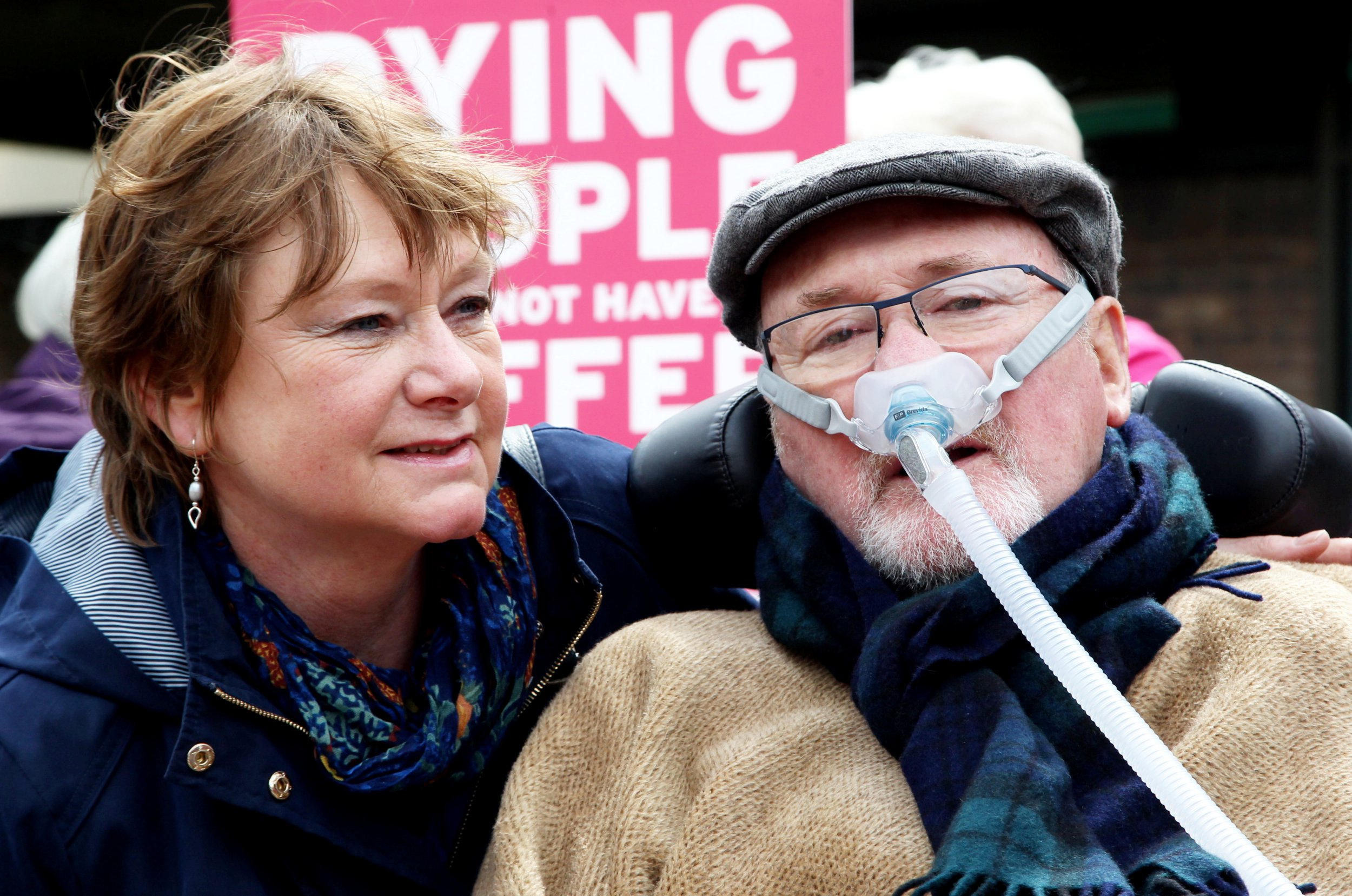 """Noel Conway with wife Carol and local supporters outside Telford County Court, Shropshire, May 1, 2018. A terminally ill man who is challenging the law on assisted suicide has asked judges to acknowledge his """"basic right to die"""" and to envisage themselves in his position. See NTI story NTIDYING. Noel Conway, 68, was speaking before his case is heard at the Court of Appeal. He has motor neurone disease (MND), an incurable, progressive, muscle-wasting condition. Diagnosed in 2014, he is in a wheelchair and has almost no movement below his neck. He wants a doctor to be allowed to prescribe him a lethal dose of drugs when he feels life has become unbearable."""