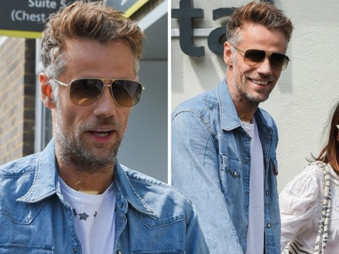 Richard Bacon flashes a smile as he leaves hospital after six-day coma
