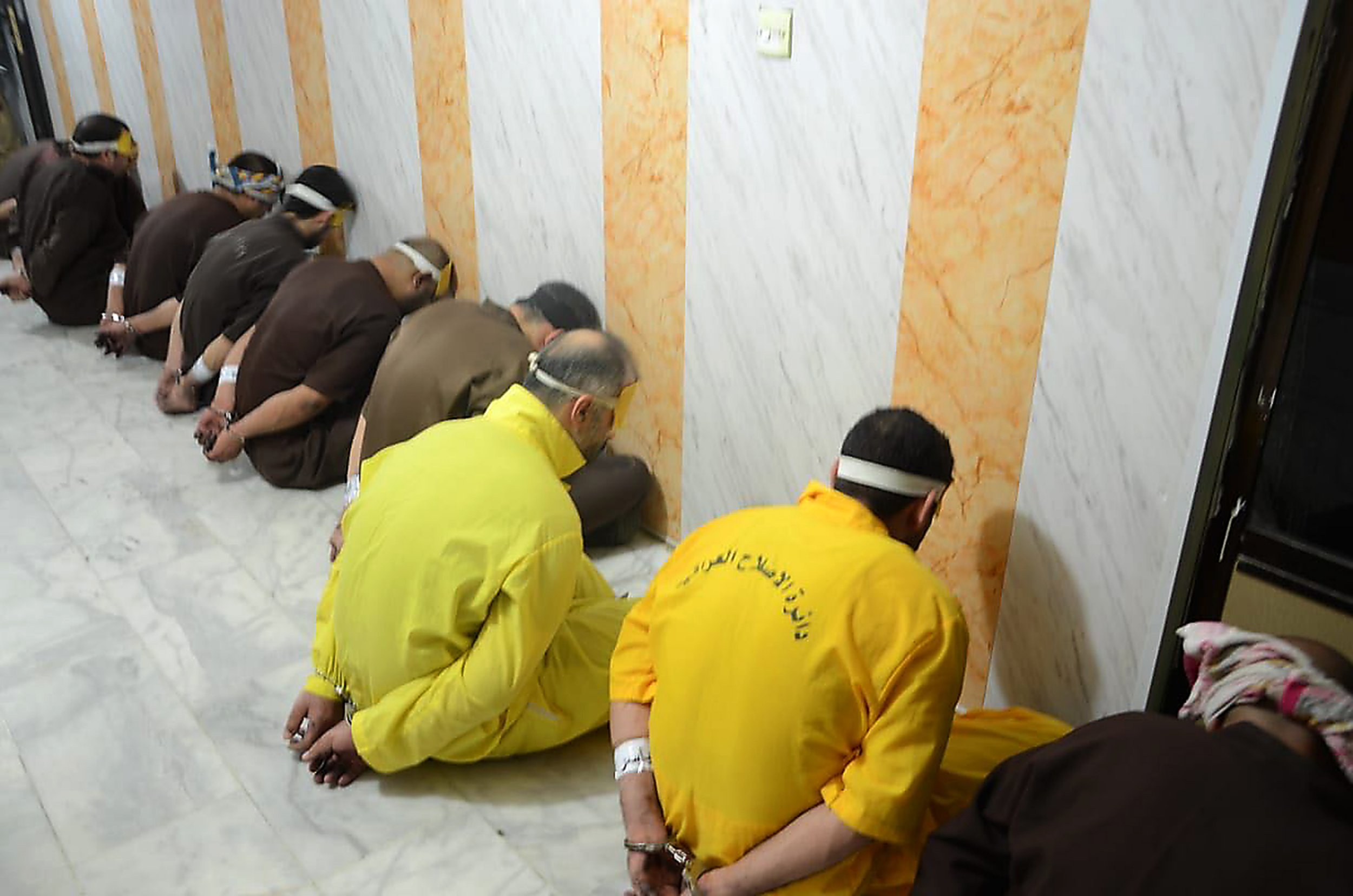 "TOPSHOT - EDITORS NOTE: Graphic content / A handout picture released by the Iraqi Justice Ministry on June 29, 2018 shows blindfolded and handcuffed jihadists of the Islamic State group who have been condemned to death waiting for their sentences to be executed. Iraq executed a dozen death row jihadists on the order of Prime Minister Haider al-Abadi, his office said today, in retaliation for the Islamic State group's execution of eight captives. The executions on June 28 came shortly after Abadi ordered the ""immediate"" implementation of the death sentences of hundreds of convicted jihadists in response to the killings by IS. / AFP PHOTO / Iraq Justice Minister / HandoutHANDOUT/AFP/Getty Images"