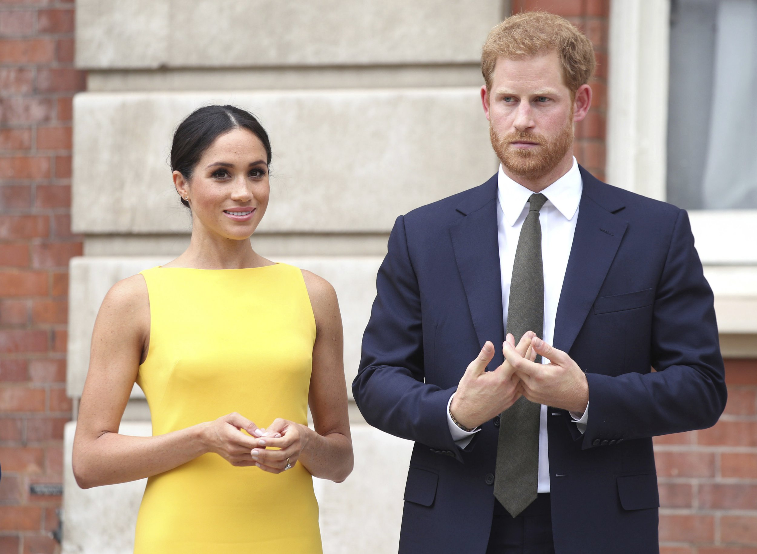 Britain's Prince Harry, the Duke of Sussex, right and Meghan, the Duchess of Sussex attend the 'Your Commonwealth' Youth Challenge reception where they will meet youngsters from across the Commonwealth, at Marlborough House in London, Thursday July 5, 2018. (Yui Mok/Pool Photo via AP)