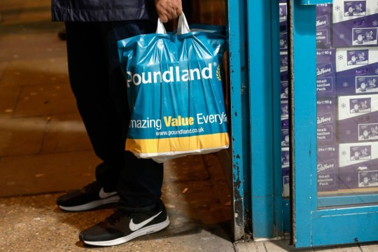 A customer carries a Poundland plastic shopping bag outside a Poundland Group Ltd. discount retail store, operated by Steinhoff International Holdings NV, in London, U.K., on Tuesday, Dec. 12, 2017. Steinhoff Chairman?Christo Wiese, seeking to stabilize the embattled retailer, is negotiating a standstill agreement on a 1.5 billion-euro ($1.8 billion) margin loan under which banks would suspend the sale of stock until next year, according to people with knowledge of the discussions. Photographer: Luke MacGregor/Bloomberg via Getty Images