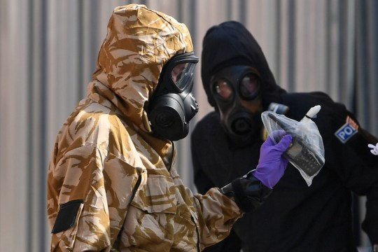 An investigator wearing a camouflaged protective suit, gloves and a gas mark works with a police investigator in a protective suit in Rollestone Street outside the John Baker House Sanctuary Supported Living in Amesbury, southern England, on July 6, 2018 in connection with the investigation after a man and woman were found unconscious in circumstances that sparked a major incident after presumed contact with what was later identified as the nerve agent Novichok. Police on July 6, 2018, raced to find the object that contaminated a British couple with the Soviet-made Novichok nerve agent in southwestern England where a former Russian spy was poisoned with the same toxin four months ago. / AFP PHOTO / Chris J RatcliffeCHRIS J RATCLIFFE/AFP/Getty Images