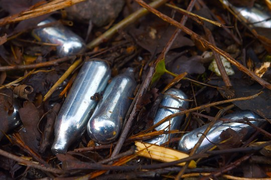 Used canisters of nitrous oxide lie on the ground