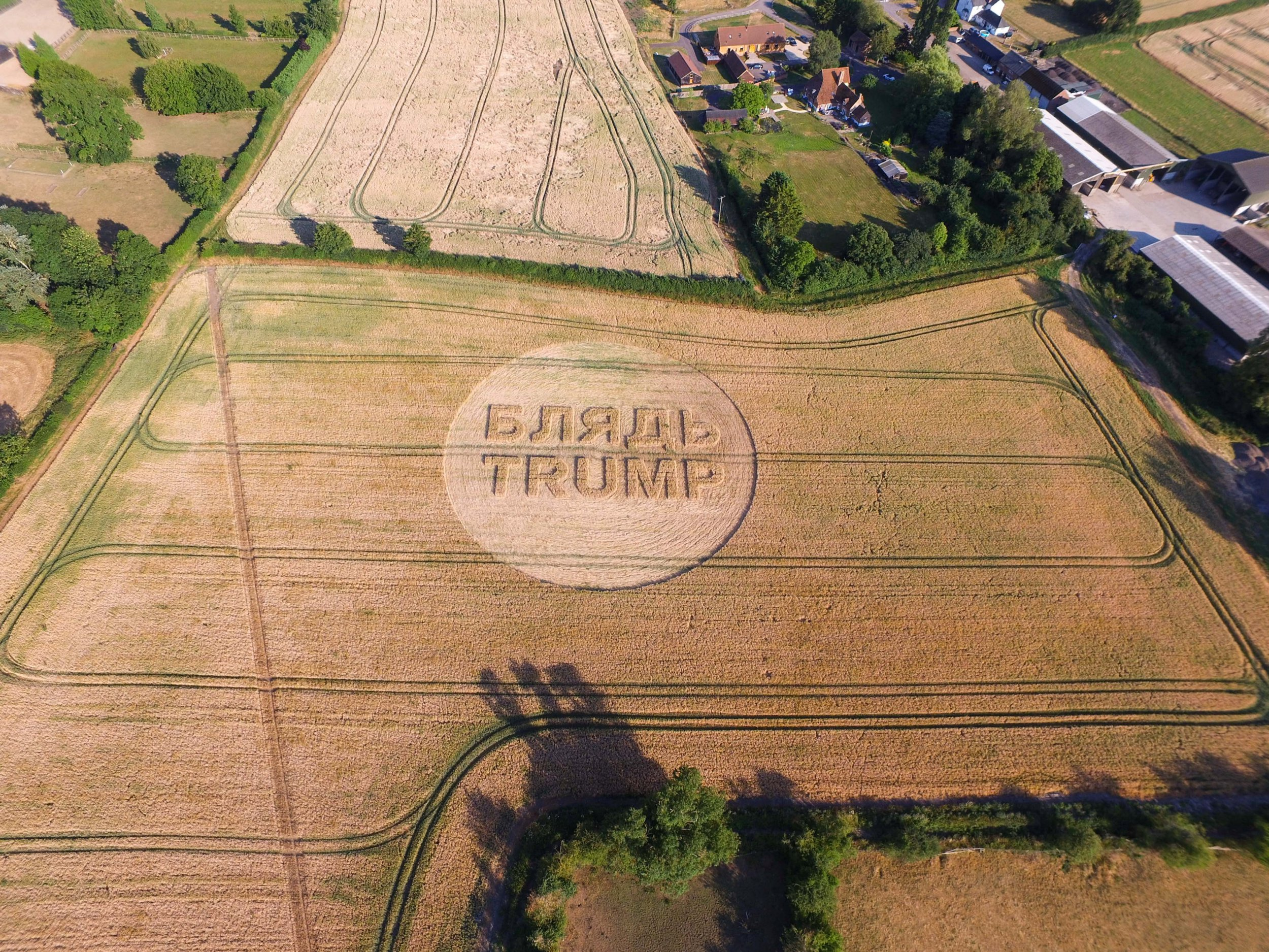 The US president will be welcomed onto British soil by a crop circle message which says ???Whore Trump???. See SWNS story SWTRUMP; President Trump will see the crop circle as he flies by helicopter to the Prime Minister???s country house on Friday. He is holding talks with Theresa May at the estate, Chequers in Buckinghamshire, before spending two days in Scotland. Drone images taken from 400ft show the message carefully shaped into farmland in Stoke Mandeville, Aylesbury. It says ????????????? Trump??? - with the first word a Russian translation for ???whore???. The people who wrote the expletive message are said to be ???crop circle experts who prefer to remain anonymous???.The photographer, who also asked to remain anonymous, said: ???The photos were taken from 400ft and the crop circle is on a farm in Stoke Mandeville, Aylesbury