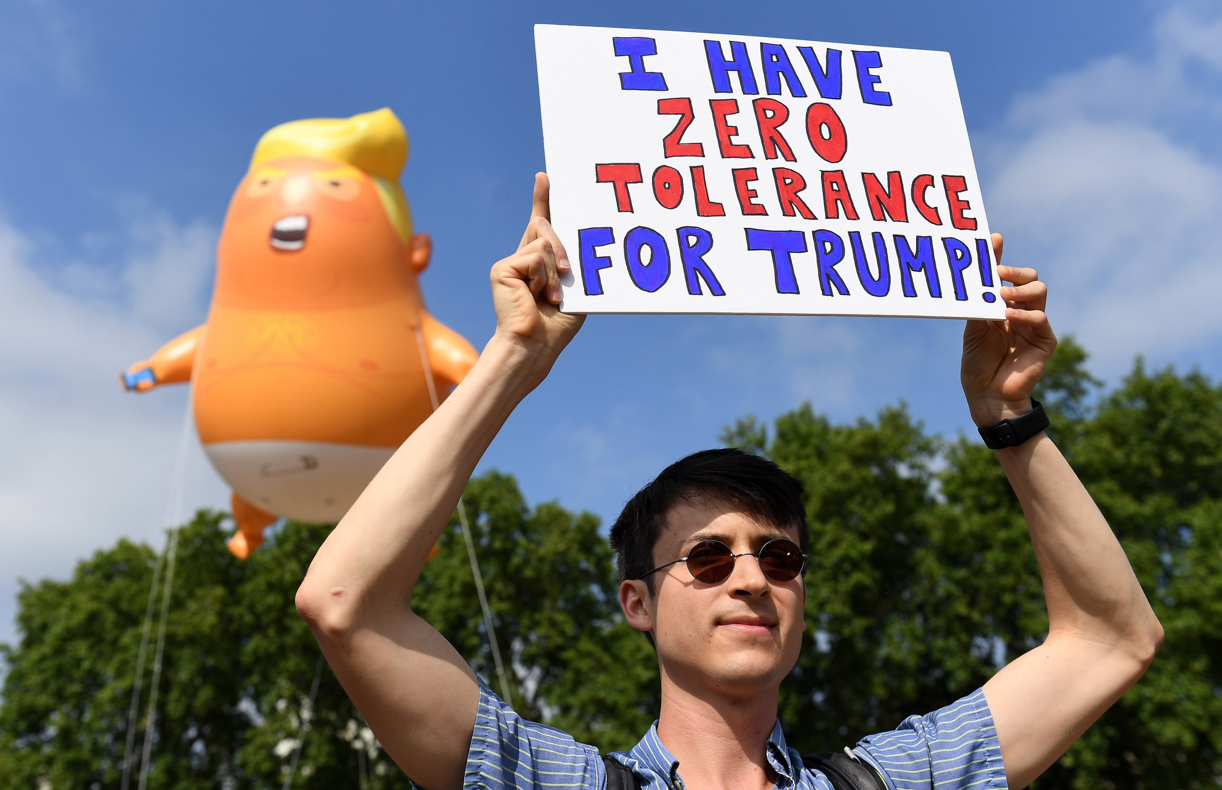 epa06885217 A protesters holds up a banner reading 'I have zero tolerance for Trump' as the 'Donald Trump Baby Blimp' balloon flies over Parliament Square during a protest in London, Britain, 13 July 2018. The inflatable dubbed 'Trump Baby' tied to a spot in Parliament Square is to kick off a day of protests against US President Donald J. Trump's visit. Trump is on a working visit to Britain. EPA/ANDY RAIN