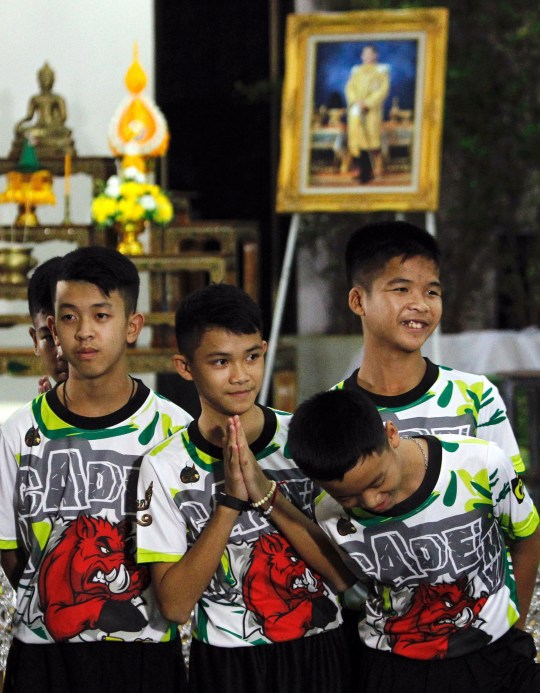 epa06896373 Some of the 12 members of the Wild Boar soccer team, who were rescued from the Tham Luang cave, greet the media during a military governmental TV pool broadcasting program at Chiang Rai Provincial Administrative Organization in Chiang Rai province, Thailand, 18 July 2018. The thirteen members of Wild Boar child soccer team, including their assistant coach, who were trapped in the Tham Luang cave since 23 June 2018, made their first appearance on the day for a tightly-controlled interview with the media after they were rescued, before returning to their homes with families. EPA/PONGMANAT TASIRI