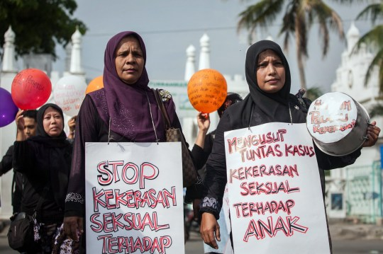"TO GO WITH Indonesia-education-crime-children,FOCUS by Arlina Arshad This photo taken on April 24, 2014 shows a group of Indonesian mothers staging a protest against child sexual abuse in Banda Aceh in Aceh province, on western Sumatra island, following incidents of child sexual abuse in Banda Aceh and in Jakarta. A sex abuse scandal at one of Indonesia's most prestigious international schools in Jakarta has sparked a heated debate about the failure to protect youngsters in the country and prompted calls for harsher punishments for paedophiles. The placard reads ""stop sexual violence against children"". AFP PHOTO / CHAIDEER MAHYUDDIN (Photo credit should read CHAIDEER MAHYUDDIN/AFP/Getty Images)"