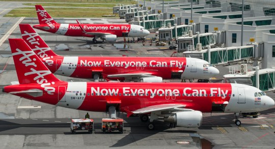 To go with AFP story Indonesia-Malaysia-Singapore-aviation-AirAsia-company,FOCUS by Satish Cheney This photo taken on January 10, 2015 shows AirAsia passenger planes parked on the tarmac at the low-cost carrier Kuala Lumpur International Airport 2 (KLIA2) in Sepang. Until Flight QZ8501 went down everything had gone right during a spectacular 13-year run of success for AirAsia, which unlocked a booming market of budget travellers in the region. AFP PHOTO / MOHD RASFAN (Photo credit should read MOHD RASFAN/AFP/Getty Images)