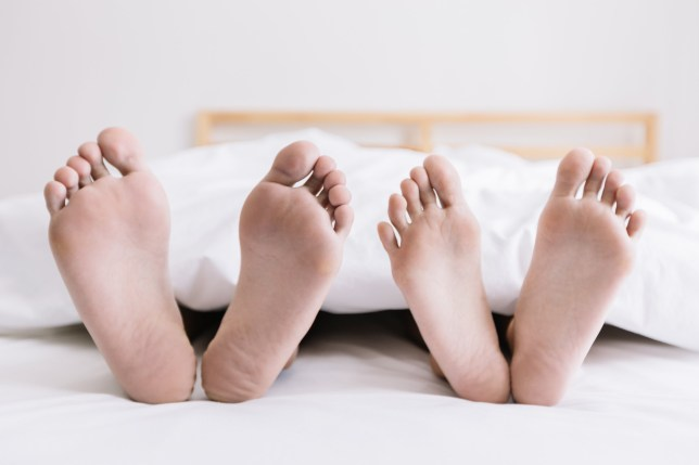 Close up of couple feet sleeping together on bedroom at early morning. Couple relaxing concept.