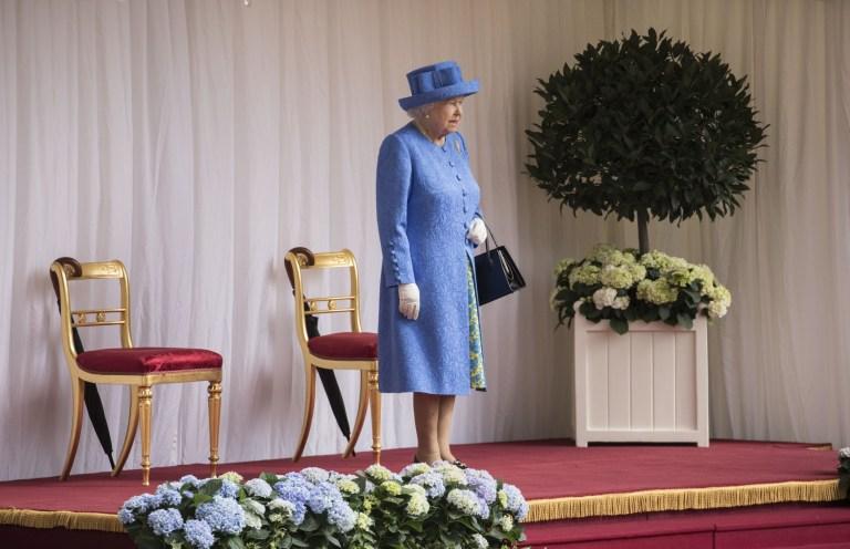 WINDSOR, ENGLAND - JULY 13: Britain's Queen Elizabeth II awaits the arrival of U.S. President Donald Trump at Windsor Castle on July 13, 2018 in Windsor, England. Her Majesty welcomed the President and Mrs Trump at the dais in the Quadrangle of the Castle. A Guard of Honour, formed of the Coldstream Guards, gave a Royal Salute and the US National Anthem was played. The Queen and the President inspected the Guard of Honour before watching the military march past. The President and First Lady then joined Her Majesty for tea at the Castle. (Photo by Richard Pohle - WPA Pool/Getty Images)