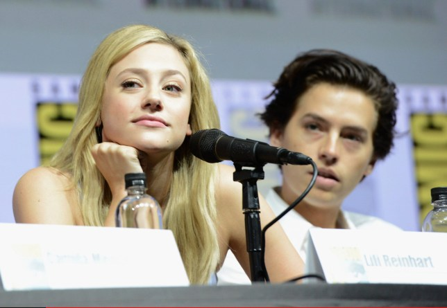 """SAN DIEGO, CA - JULY 22: Lili Reinhart (L) and Cole Sprouse speak onstage at the """"Riverdale"""" special video presentation and Q&A during Comic-Con International 2018 at San Diego Convention Center on July 22, 2018 in San Diego, California. (Photo by Albert L. Ortega/Getty Images)"""