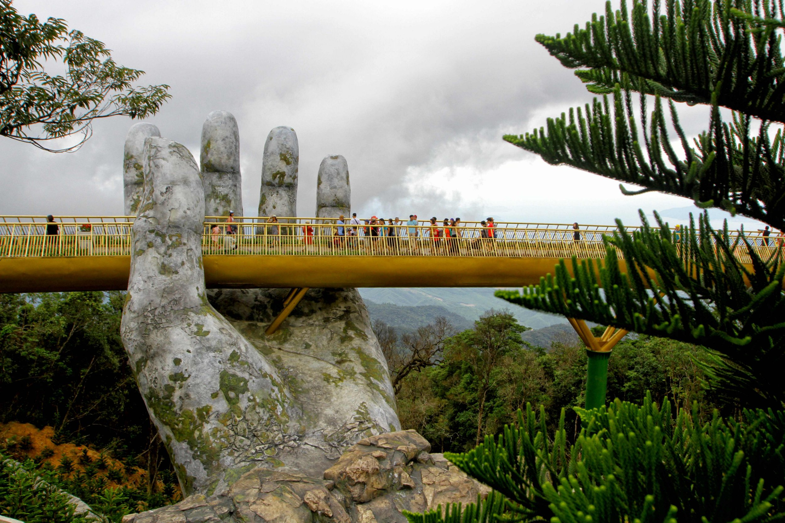 """In this photograph taken on July 31, 2018, visitors walk along the 150-meter long Cau Vang """"Golden Bridge"""" in the Ba Na Hills near Danang. Nestled in the forested hills of central Vietnam two giant concrete hands emerge from the trees, holding up a glimmering golden bridge crowded with gleeful visitors taking selfies at the country's latest eccentric tourist draw. / AFP PHOTO / Linh PHAMLINH PHAM/AFP/Getty Images"""