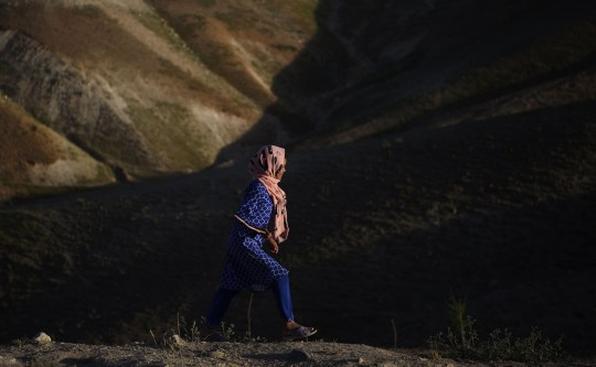 An Afghan girl walks on a hilltop on the outskirts of Kabul on July 21, 2017. / AFP PHOTO / WAKIL KOHSAR (Photo credit should read WAKIL KOHSAR/AFP/Getty Images)