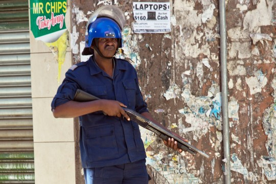 A Zimbabwean police officer cordons off the streets around the MDC opposition party headquarters in Harare, Zimbabwe, Thursday Aug. 2, 2018. Zimbabwe's acting President said Thursday that his government had been in touch with the main opposition leader in an attempt to ease tensions after election related violence in the capital. (AP Photo/Jerome Delay)