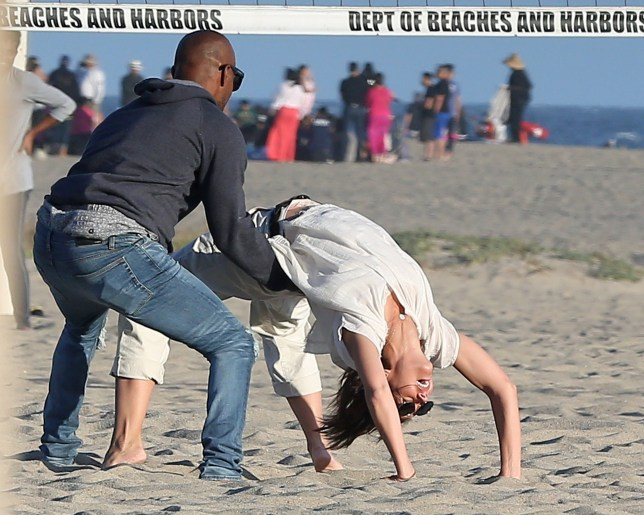 """EXCLUSIVE: **MINIMUM REPRO FEE 500 POUNDS PER IMAGE STRICTLY NO WEB** Katie Holmes and Jamie Foxx show they???re still very much head over heals in love as they frolic on the beach almost a year after being seen in public for the first time. The amazing pictures show the loved-up Hollywood couple kissing and cuddling during a romantic summer date in front of dozens of other beach-goers. The notoriously private duo couldn???t hide their affections for each other as they smooched while lying on a blanket in the sand before playing volleyball and a game of beach tennis. And Katie collapsed on the sand in laughter after attempting to bend backwards over Jamie???s outstretched arms. The couple - who have been linked together since 2013 - looked like they didn???t have a care in the world as they frolicked and wrestled with each other in front of onlookers in Malibu, California. And the romance has clearly put a smile on the face of Katie, 39, who was seen literally doing a cartwheel while laughing. An onlooker said: ???Katie and Jamie looked like every other couple in love and were clearly not hiding their affection for each other. ???She had this incredible smile on her face and looked smitten. It???s hard to think of her looking this happy in a while. ???At one point Jamie held her while she did an backwards yoga pose and they then fooled around while playing tennis and volleyball. ???They then lay down on a blanket and a bottle of champagne was near them. It looked like the perfect summer???s evening."""" Katie looked beach casual in a white t-shirt and cream pants while Jamie, 50, rocked a pair of blue denim jeans and a gray hooded sweatshirt. The pair have been linked since a year after Katie ended her six year marriage to Mission Impossible star Tom Cruise. The very private couple have reportedly been dating since being spotted dancing together at the Hamptons a year after the Dawson Creek star's highly-publicised separation from Cruise. They have taken extraordinary"""