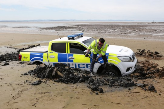 MERCURY PRESS. 06/08/18. Crosby, UK. A Port Of Liverpool Police truck is left stranded on Crosby Beach in Merseyside today after getting into difficulty during a late night drive on the beach last night. The vehicle, a Nissan pick-up truck, is thought to cost upwards of ?25,000 pounds. Following there embarrassing incident the truck will now be written off after being fully submerged in seawater. Photo Credit: Ian Hinchliffe/Mercury Press