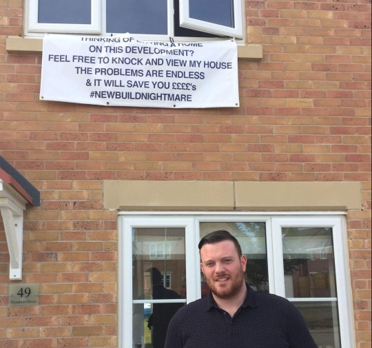 Pics from Caters News - (Pictured: Mike Firth, 31 standing in front of the sign) -A disgruntled first time home owner has turned vigilante by hanging a huge sign from the window of his new build to warn off other buyers.Dad-of-three Mike Firth, 31, paid 220,000 for a four-bedroom home on the Sycamore Gardens estate in Castleford, West Yorks which was supposed to be a dream first home for his young family when they moved in in April 2017.SEE CATERS COPY