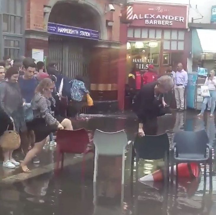 Picture from a video showing the flooding outside Hammersmith tube station. Chairs have been used as a bridge. Link to video: https://www.dropbox.com/s/sts676qjlw6g87s/Hammersmith_Flood_TRIANGLENEWS.MOV?dl=0 Full permissions give for distribution. TRIANGLE NEWS 0203 176 5581 // contact@trianglenews.co.uk COMMUTERS were forced to climb over chairs to leave a tube station this evening after heavy flooding made roads impassable. Those trying to leave Hammersmith Station in west London had to clamber one by one over chairs provided by a nearby branch of Pret-a-Manger to avoid getting soaked. Transport for London urged passengers to avoid the station after inches of rain fell in under an hour as the rush hour got underway. - full story filed via the wires
